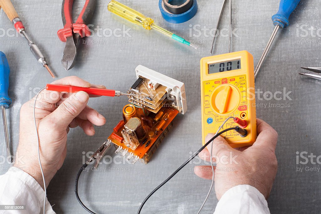 Hand of electrician with multimeter probe at  electrical switchgear cabinet stock photo