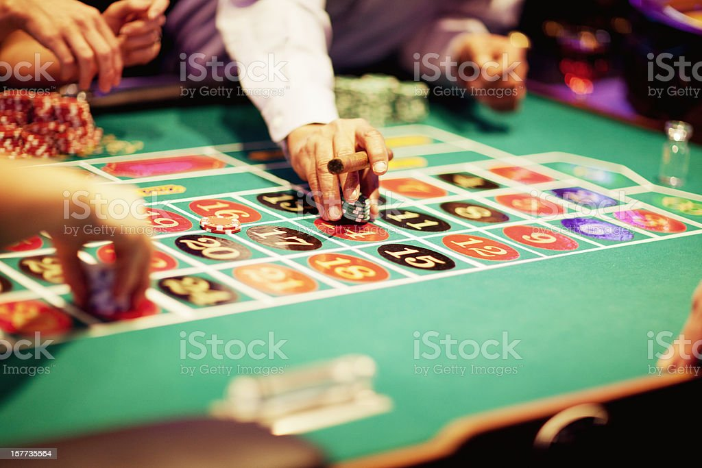 Hand of gambler making a bet at roulette table royalty-free stock photo