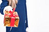 Hand of Little Blond Girl Giving Christmas Gift Box