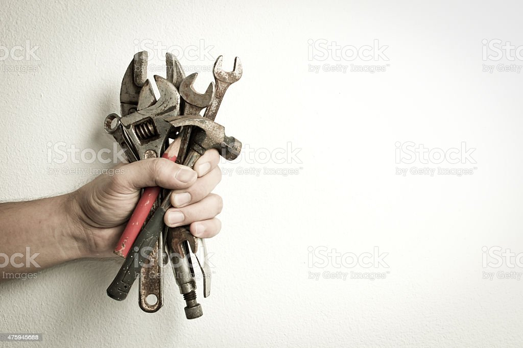 Hand of male holding old tools. stock photo