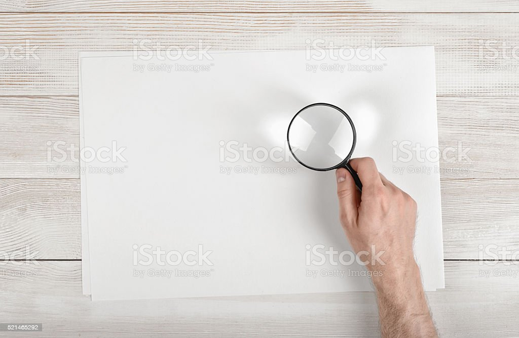 Hand of man holding the magnifying glass over white paper stock photo