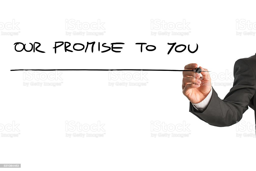 Hand of man writing Our promise to you stock photo