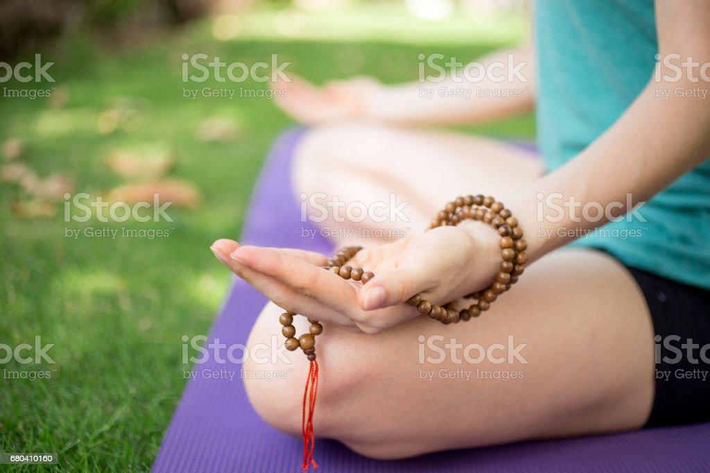Hand of meditating woman holding rosary beads stock photo