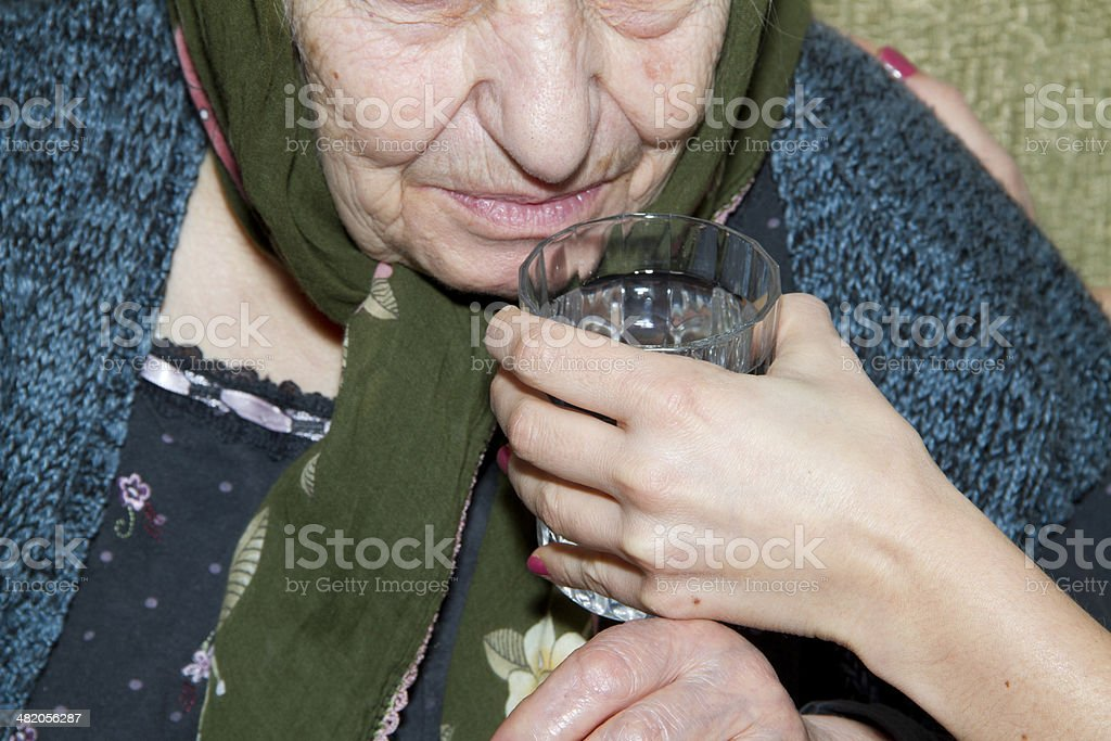 Hand of nurse giving patient medication and water stock photo