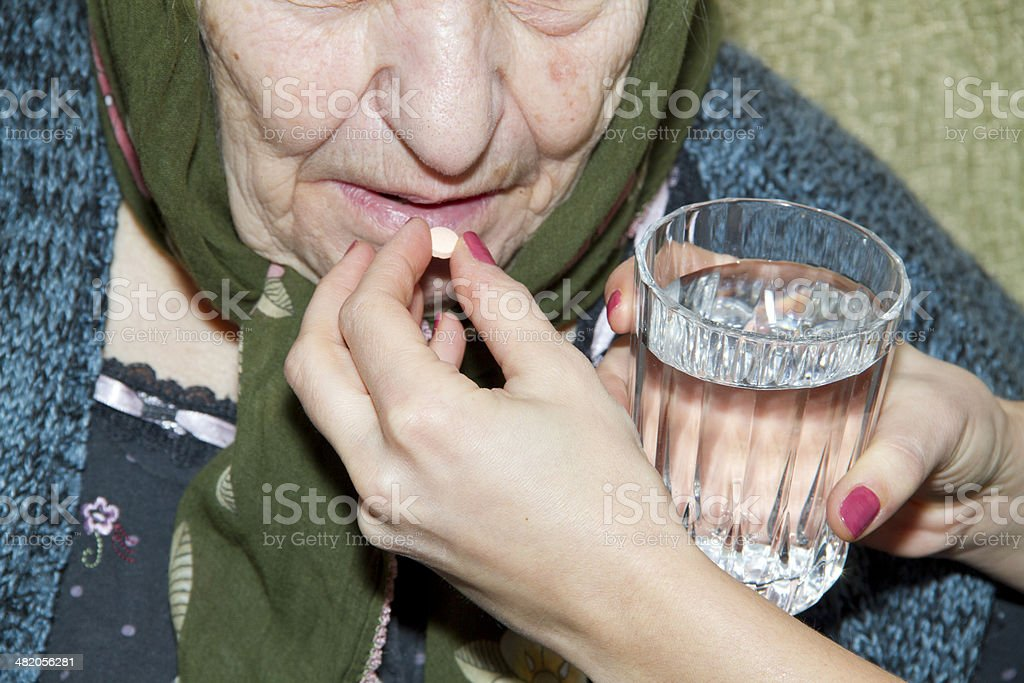 Hand of nurse giving patient medication royalty-free stock photo