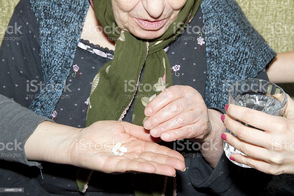 Hand of nurse giving patient medication stock photo