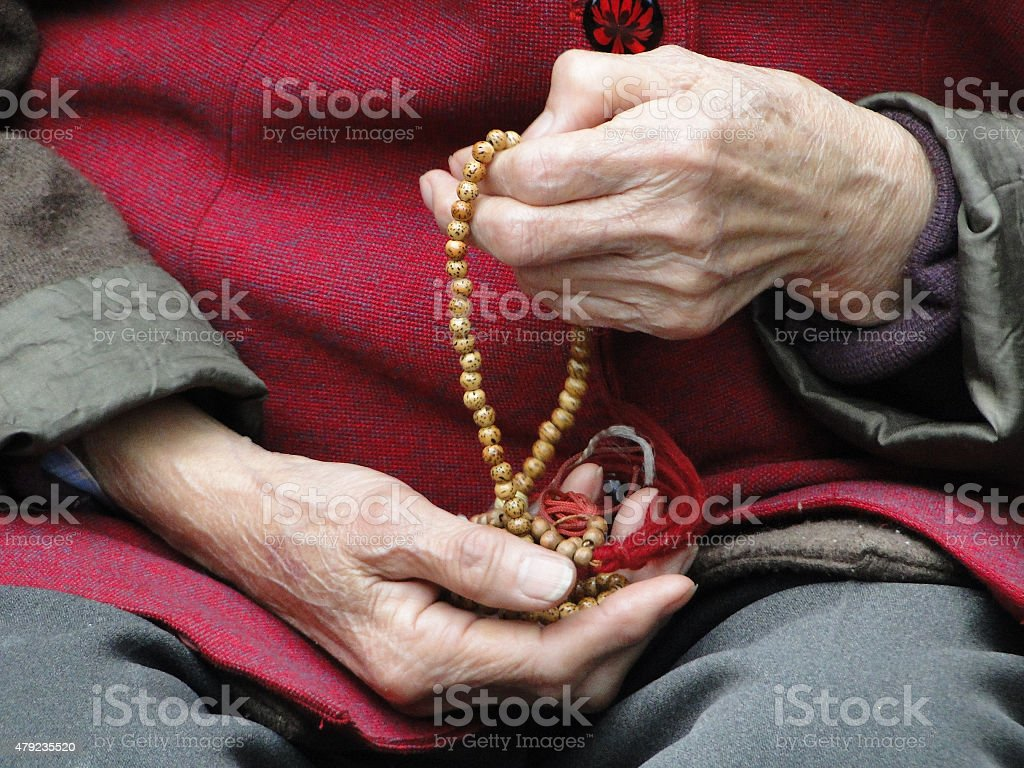 Hand of old Chinese woman by prayer of rosary stock photo
