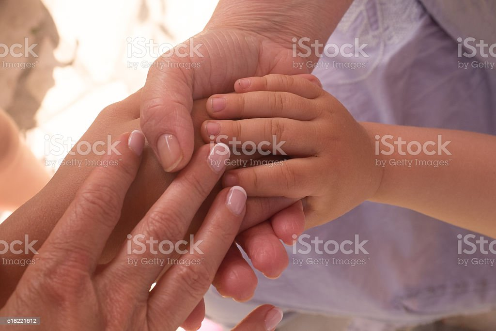 hand of old woman and young woman and child stock photo