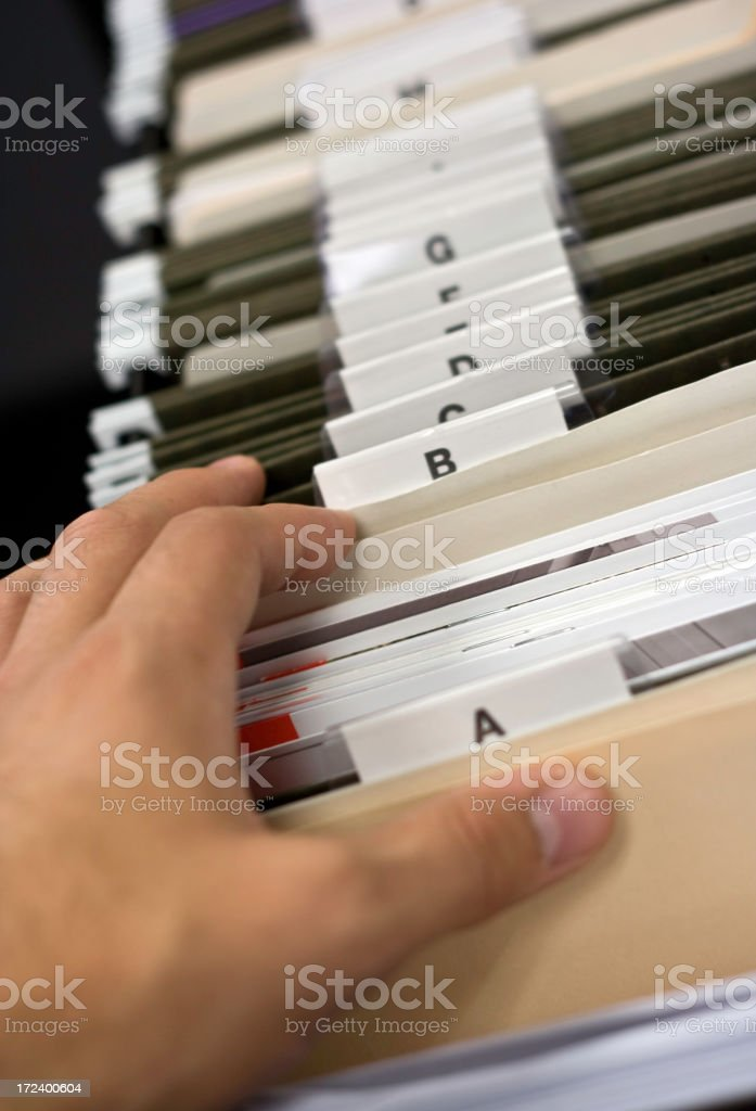 Hand of Person Looking for a Document in File Cabinet royalty-free stock photo