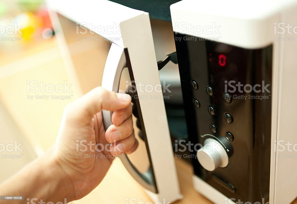 Hand of person opening a microwave oven stock photo