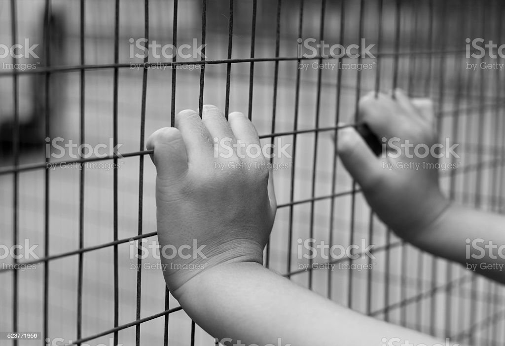 Hand of prisoner grabbed the metal fence stock photo