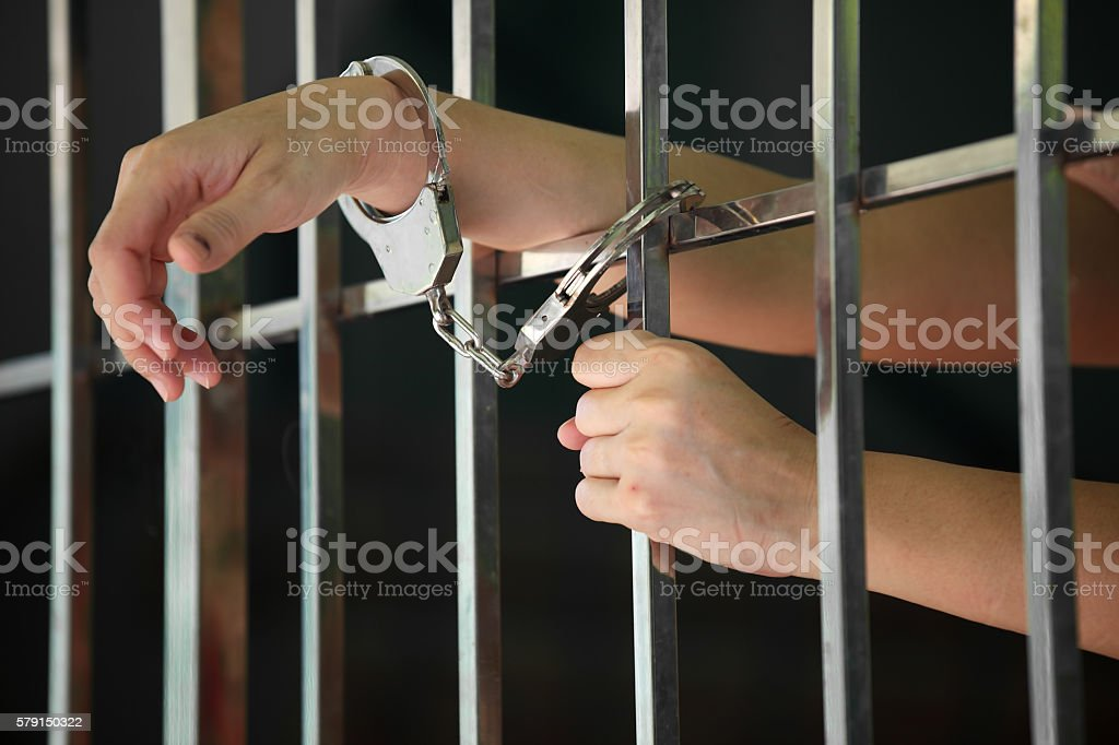 hand of prisoner in jail stock photo