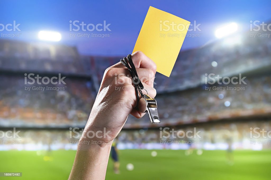 Hand of referee with yellow card and whistle stock photo