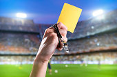 Hand of referee with yellow card and whistle