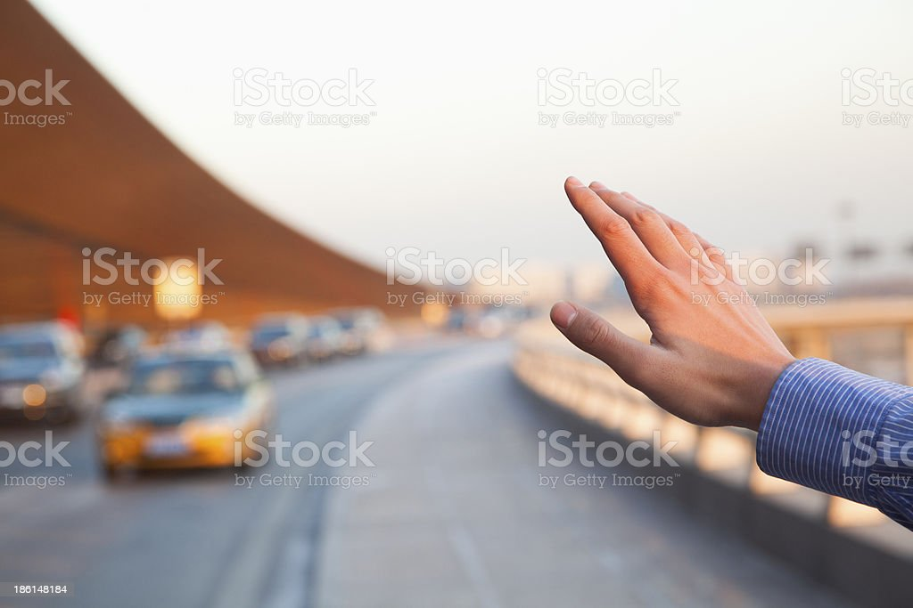 Hand of traveler hailing a taxi outside the airport royalty-free stock photo