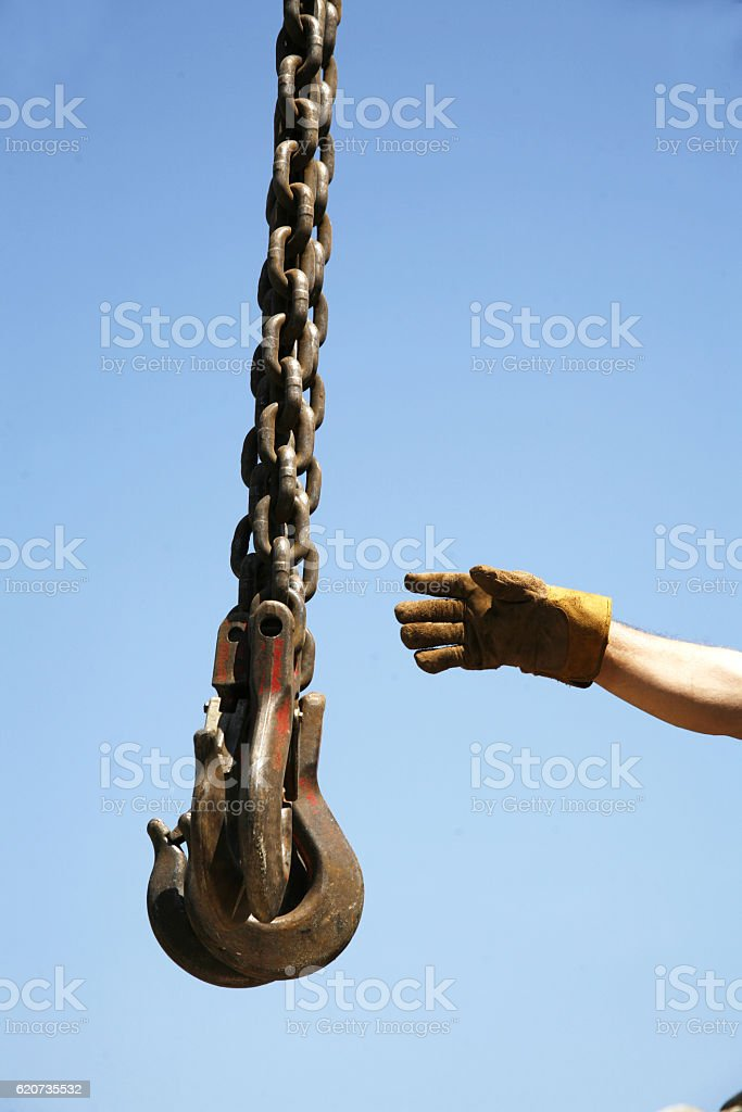 Hand of unknown worker with industrial crane chains stock photo