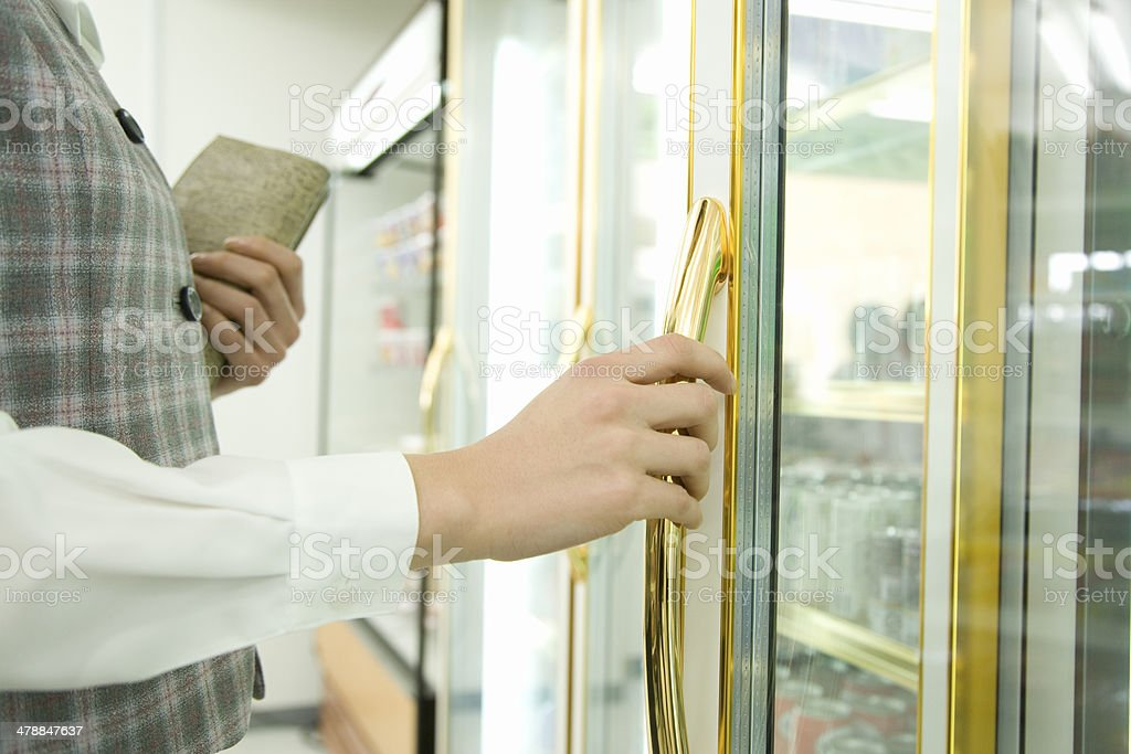 Hand of woman doing some shopping at convenience store stock photo