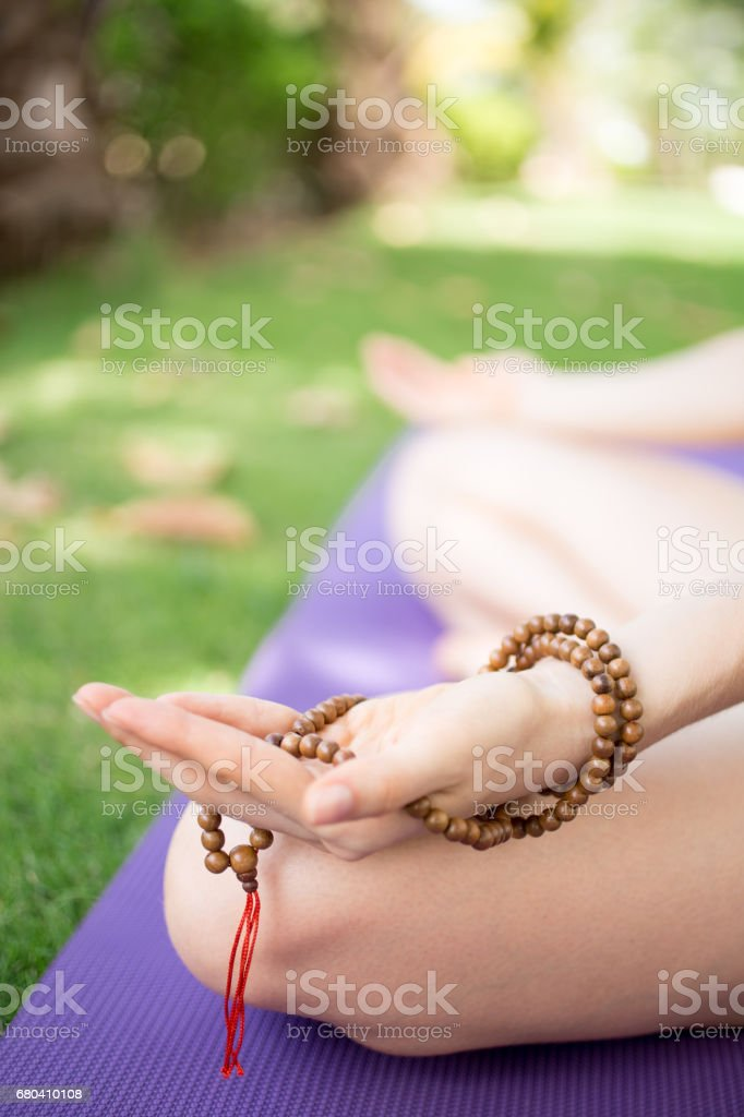Hand of woman holding rosary beads and meditating stock photo
