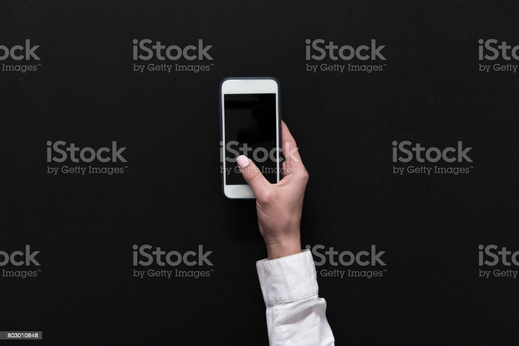 hand of woman holding smartphone with blank screen isolated on black stock photo