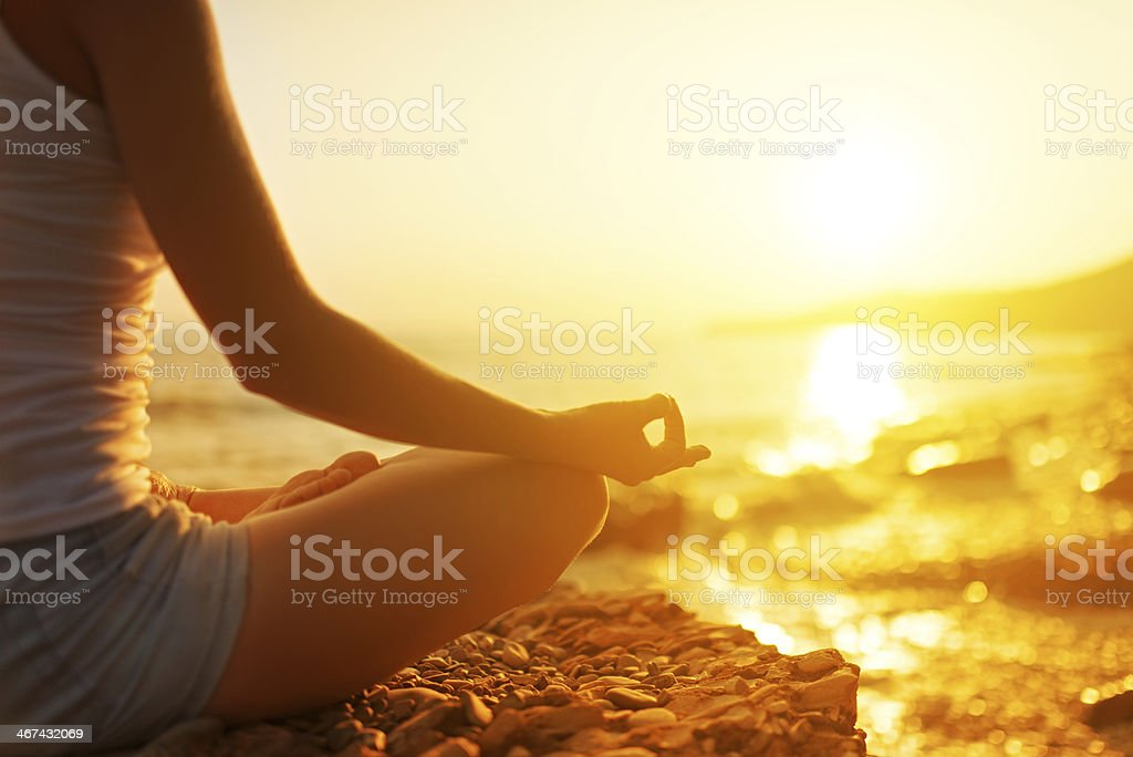 hand of  woman meditating in a yoga pose on beach stock photo