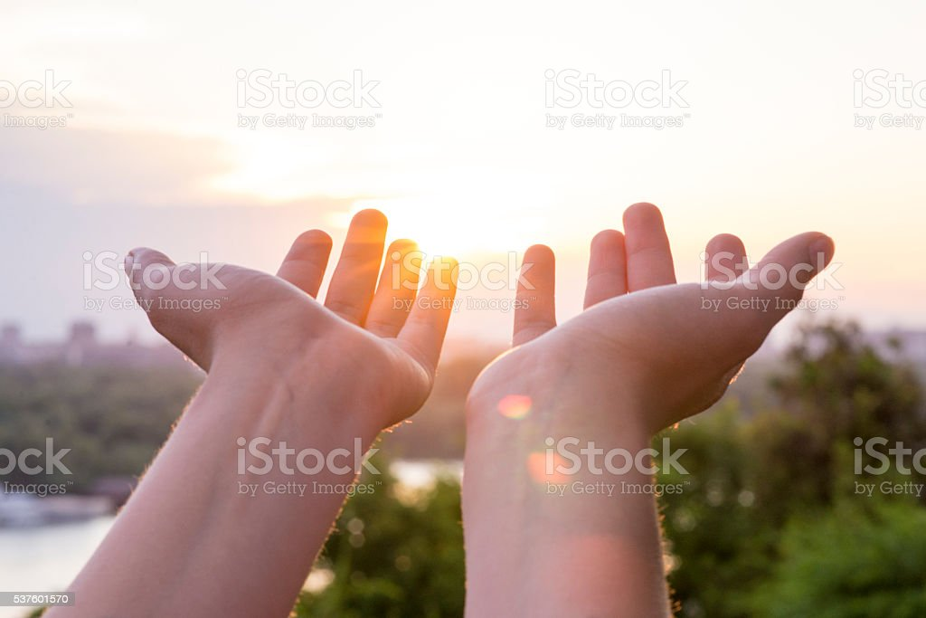 Hand of woman reaching to towards sky. Color toned image stock photo