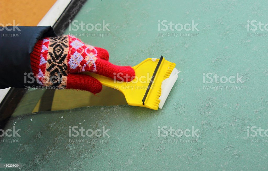 Hand of woman scraping ice from car windscreen stock photo