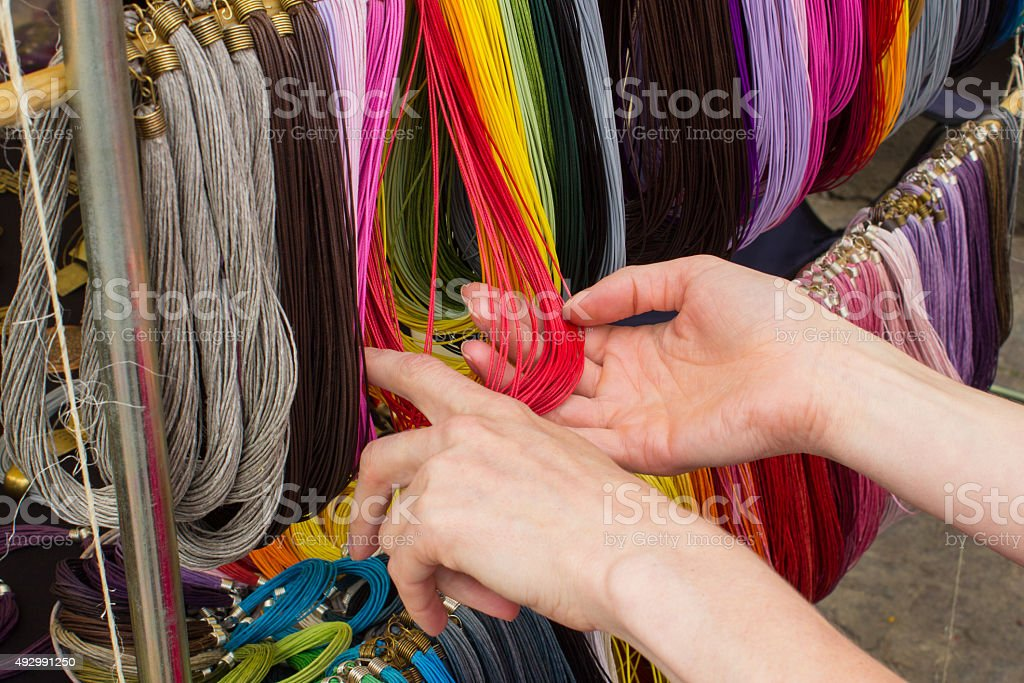 Hand of woman with colorful necklace at the bazaar stock photo
