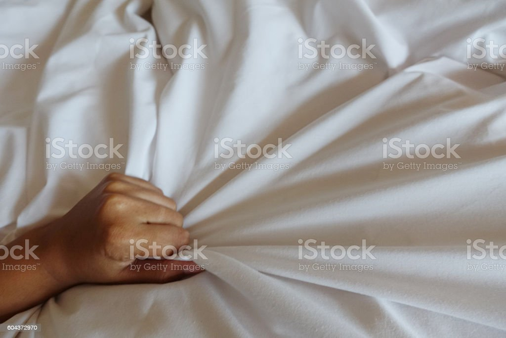 hand of women pulling white sheets in ecstasy, orgasm. stock photo