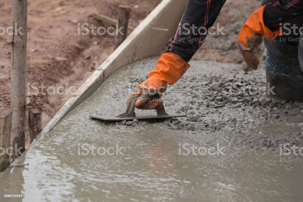 hand of worker use trowel plastering a newly concrete floor stock photo