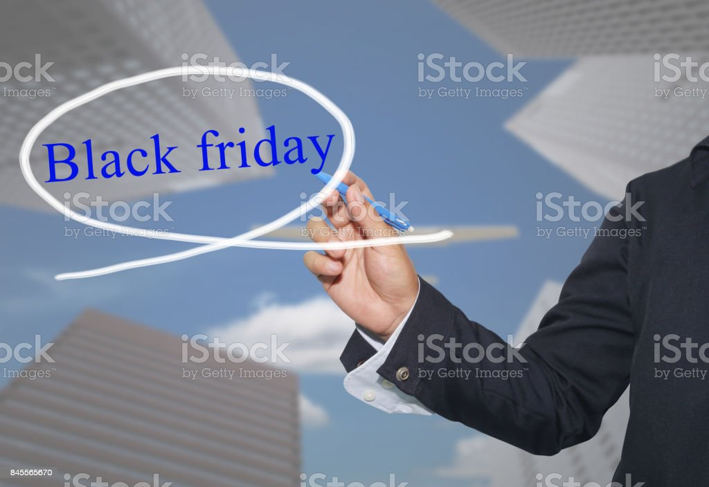 Hand of young businessman write the word Black Friday on skyscrapers background. stock photo