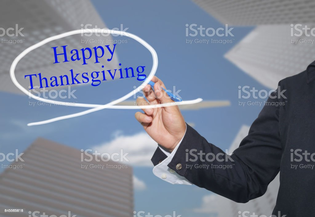 Hand of young businessman write the word Happy Thanksgiving on skyscrapers background. stock photo