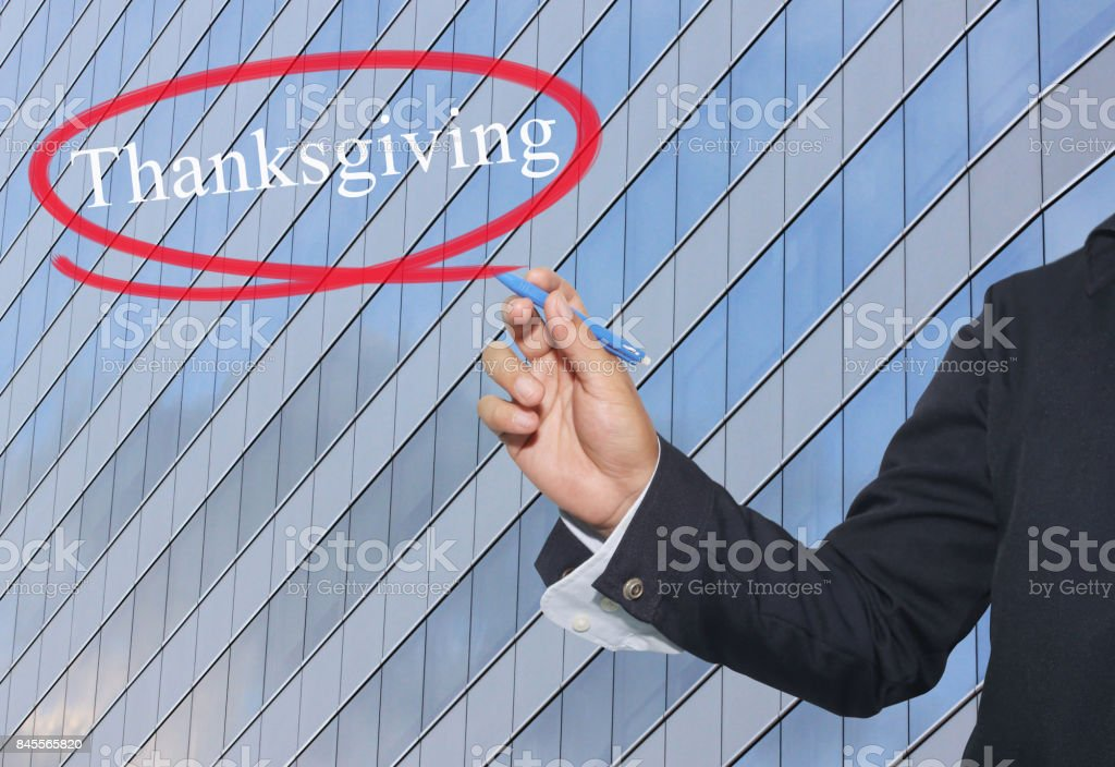 Hand of young businessman write the word Thanksgiving on skyscrapers background. stock photo