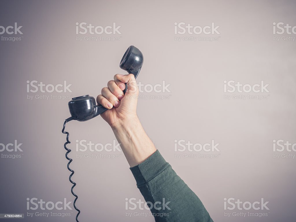 Hand of young man holding vintage phone stock photo