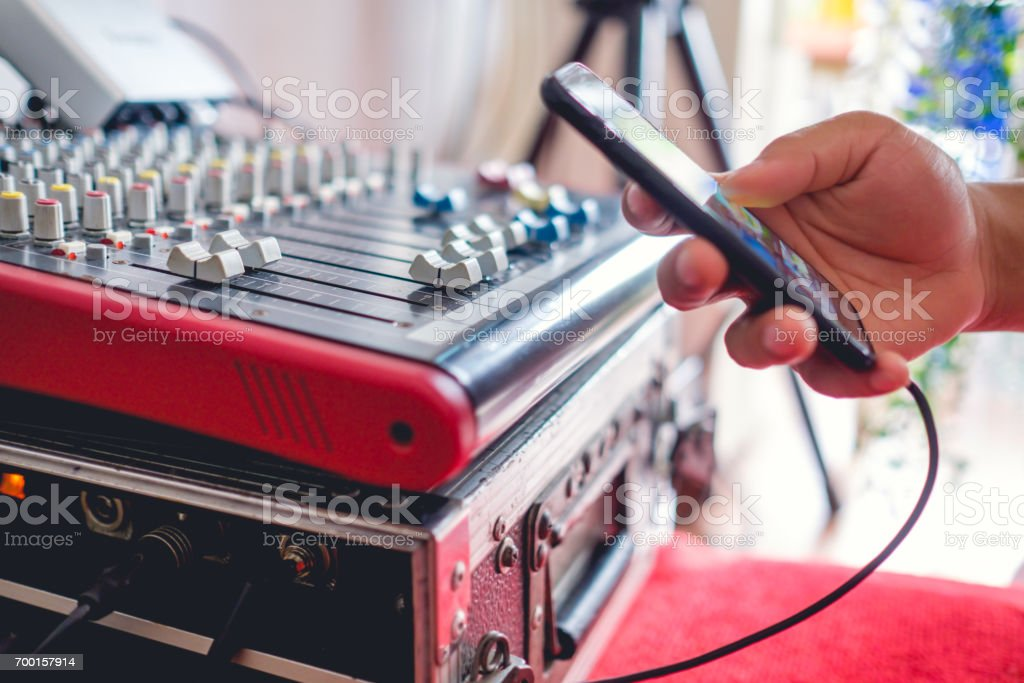 Hand of young man using music application in smartphone turn on the music with the music mixer stock photo