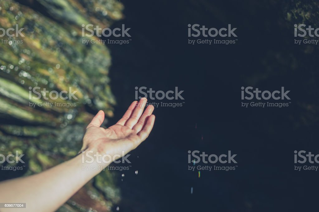 Hand of young woman touching water drops stock photo