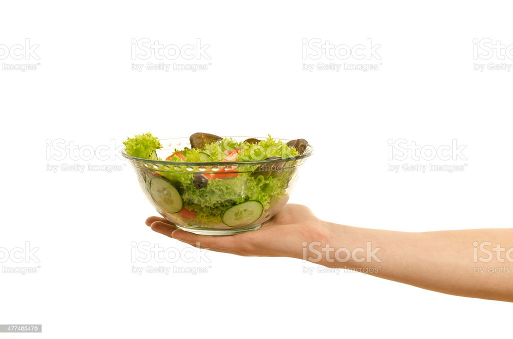 Hand offering a bowl of organic salad isolated on white. stock photo
