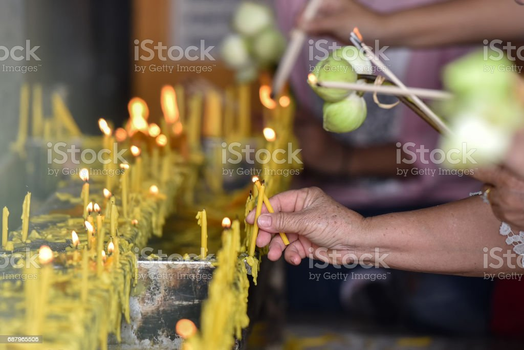 hand old woman hold candle Buddha in temple stock photo