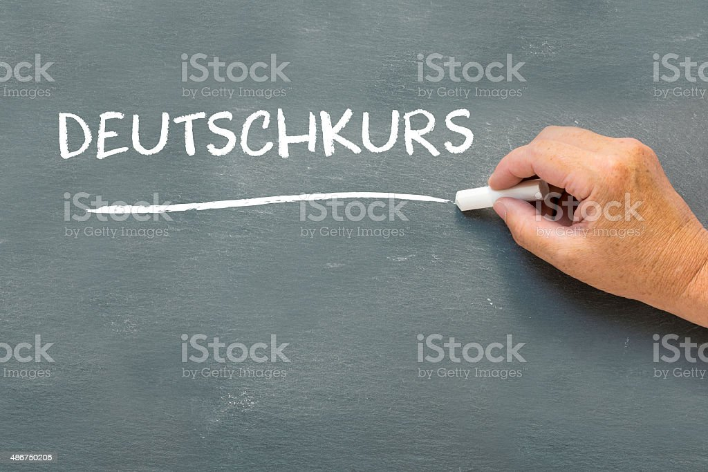 Hand on a chalkboard with the German word Deutschkurs stock photo