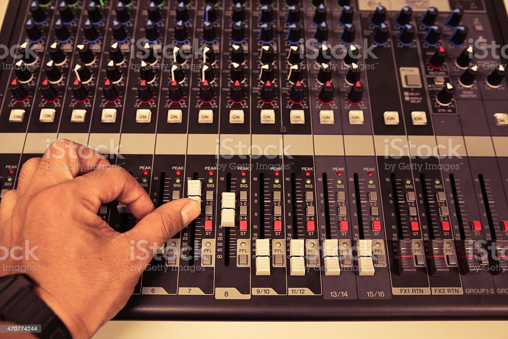 Hand on a Mixing Desk with vintage picture style, stock photo