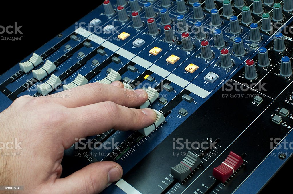 hand on an audio mixer stock photo