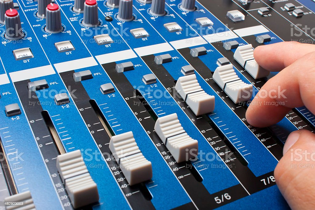 Hand on Blue mixing board faders and knobs royalty-free stock photo