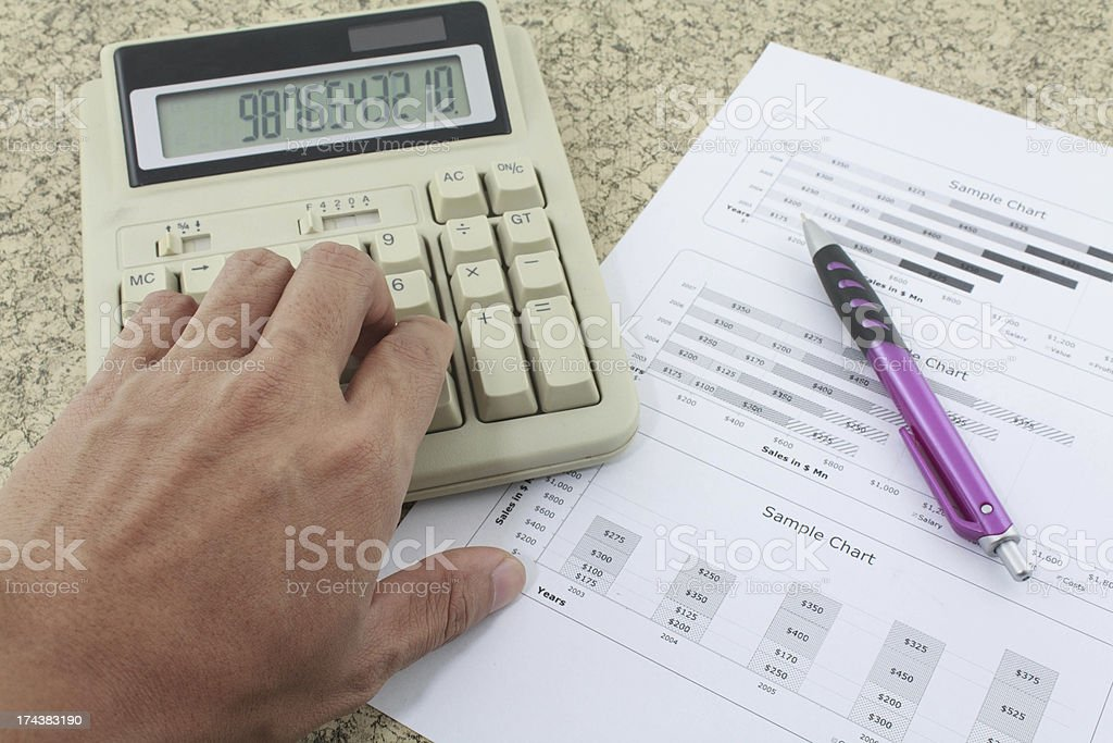hand on calculator paper and pen royalty-free stock photo