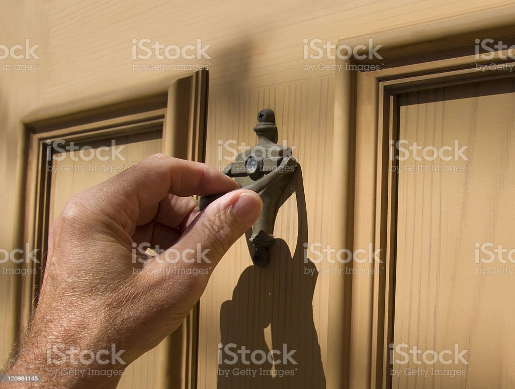 hand on door knocker stock photo