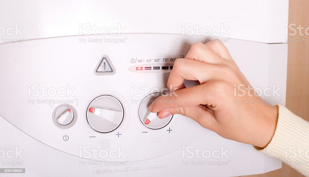 Hand on gas boiler stock photo