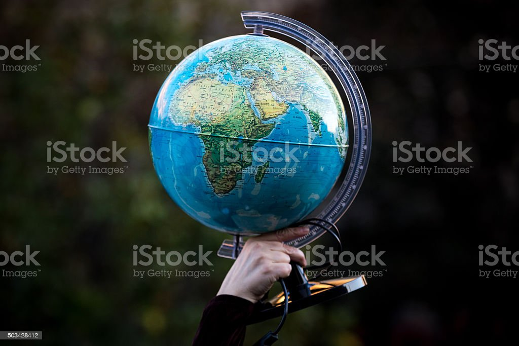 Hand on globe stock photo