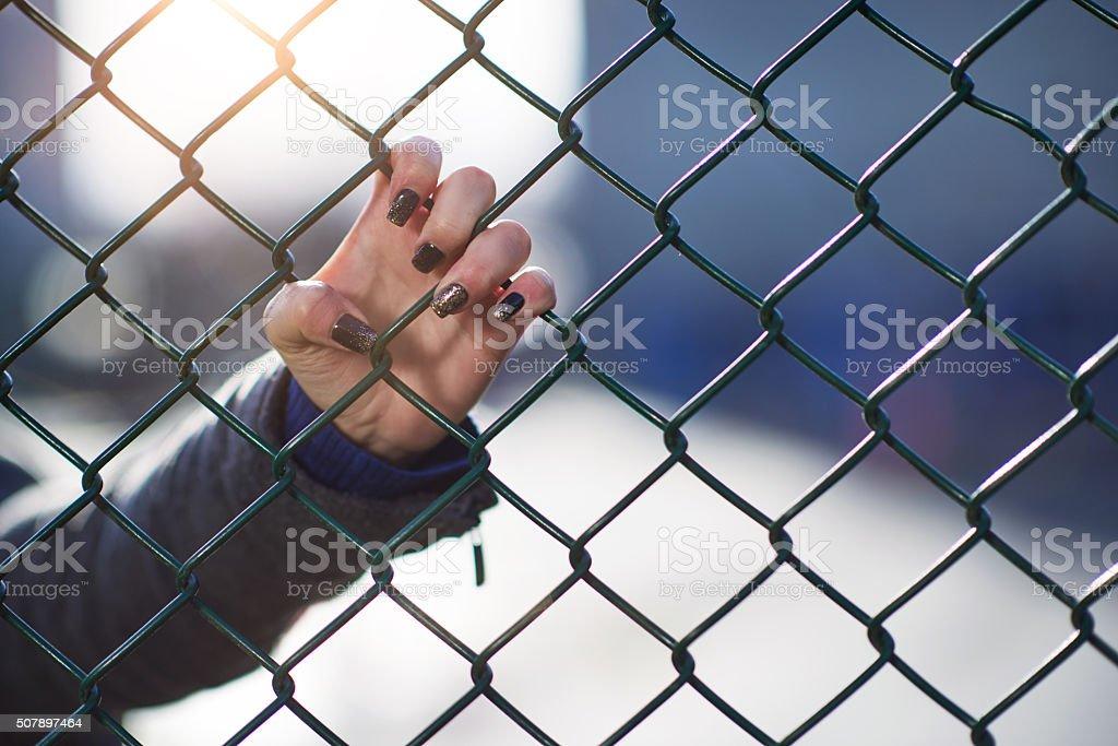 hand on iron fence stock photo