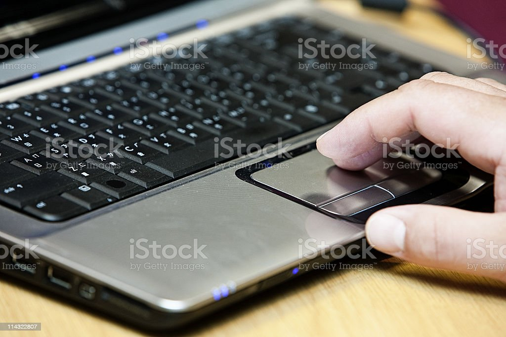 Hand on laptop track pad stock photo