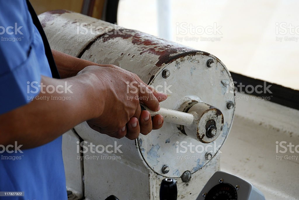 Hand on lever of a ferry in Mekong Delta stock photo