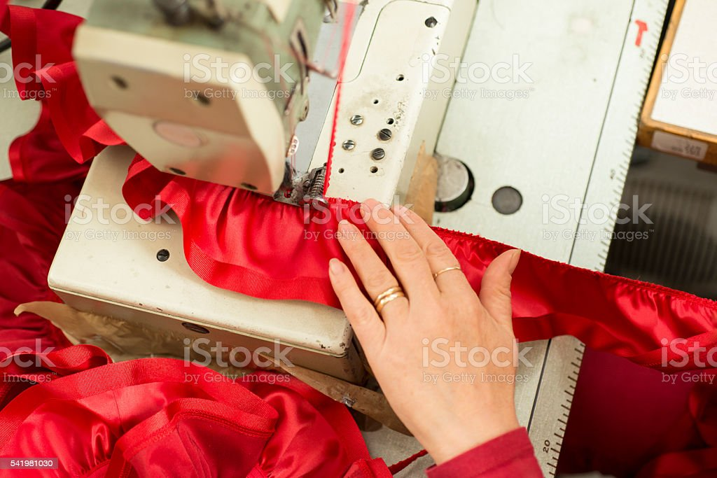 Hand on Sewing Machine Stitching Red Ribbon and Ruffled Cloth stock photo