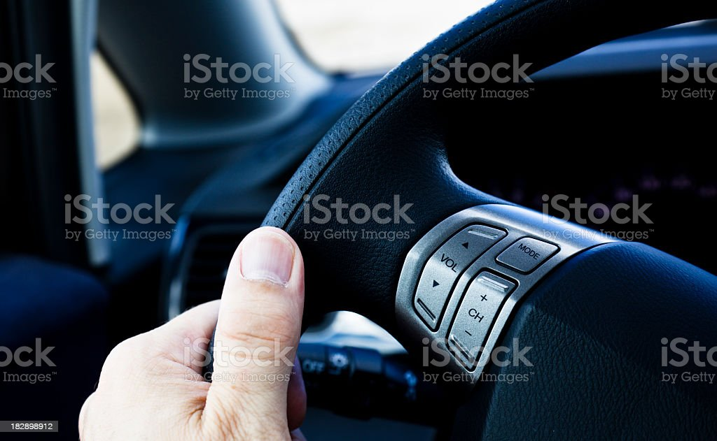 Hand on steering wheel with radio buttons. Driving the car. royalty-free stock photo